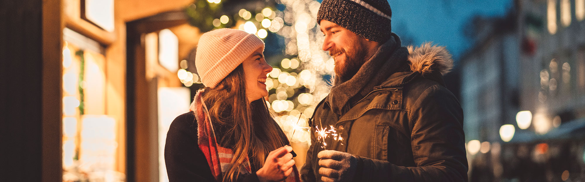Couple at christmas holding sparklers.